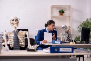A young male employee with skeletons in the office.